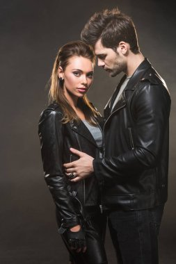 beautiful couple in leather jackets embracing on dark background