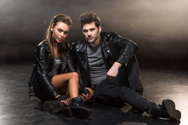 beautiful fashionable couple in leather jackets sitting and posing on dark background