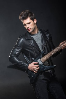 handsome rocker in leather jacket playing electric guitar isolated on black