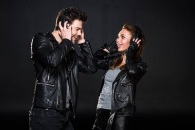 beautiful smiling couple in headphones and leather jackets listening music isolated on black