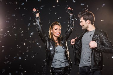 beautiful couple in leather jackets cheering with falling confetti on black background
