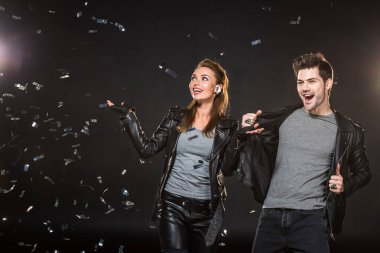 beautiful happy couple in leather jackets cheering with falling confetti on black background