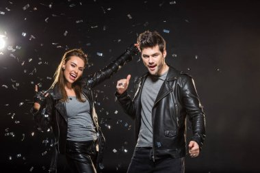 beautiful couple in leather jackets showing rock and thumb up signs while cheering with falling confetti on black background