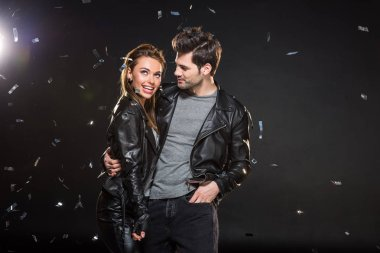 beautiful couple in leather jackets hugging with falling confetti on black background