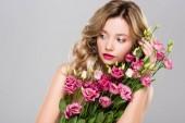 meztelen gyönyörű szőke nő pózol a tavaszi Eustoma virág csokor és látszó el elszigetelt a szürke
