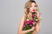 nude beautiful woman posing with spring Eustoma flowers bouquet isolated on grey