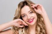 Nude usměvavá mladá žena pózuje izolované na šedá