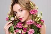 Fotografia donna nuda bella primavera holding Eustoma fiori isolati su grigio