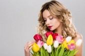 Fotografie young attractive spring woman looking at bouquet of colorful tulips isolated on grey