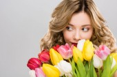 young beautiful spring woman holding bouquet of colorful tulips isolated on grey