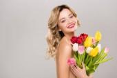 mladá usměvavá nahé atraktivní jarní žena držící kytice barevné tulipány izolované Grey