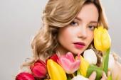 mladé jarní žena drží kytici barevných tulipánů izolované Grey nabídkového řízení