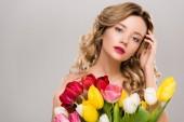 mladé nahé jarní žena drží kytici barevných tulipánů a dotýká vlasů izolované Grey