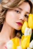 young beautiful spring woman with bouquet of yellow tulips