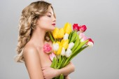Fotografie young nude spring woman holding bouquet of multicolored tulips isolated on grey