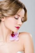 Fotografia dolce giovane donna con lorchidea viola sulla spalla isolata su grey