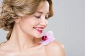 Fotografie junge lächelnd nackte Frau mit lila Orchidee auf Schulter isoliert auf grau