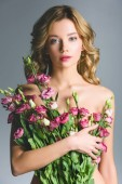 elegantní nahá žena drží kytici květin, izolované Grey