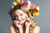 smiling woman with wreath of flowers on hair isolated on grey