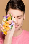 Fotografie handsome man with closed eyes covering one eye with flowers on hand isolated on beige