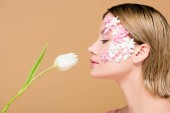side view of elegant woman with flowers on face smelling tulip isolated on beige