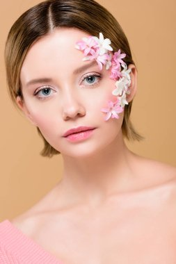 Beautiful girl with flowers on face looking at camera isolated on beige stock vector
