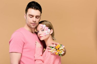 Handsome man with closed eyes embracing attractive girlfriend with flowers on face isolated on beige stock vector