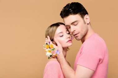 tender man with alstroemeria flowers on hand touching face of attractive girlfriend isolated on beige