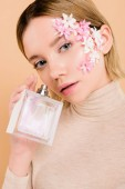 Fotografie attractive woman with flowers on face holding bottle of perfume in hand isolated on beige