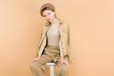 trendy woman in beret sitting on chair isolated on beige
