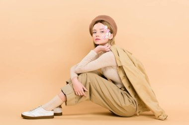 attractive girl in beret posing while sitting on floor isolated on beige
