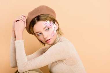 Attractive woman with flowers on face wearing beret isolated on beige stock vector