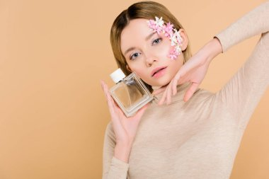 attractive woman with flowers on face posing with bottle of perfume isolated on beige