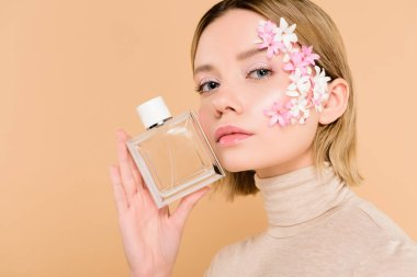 Beautiful woman with flowers on face holding bottle of perfume isolated on beige stock vector
