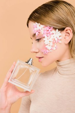 Attractive with flowers on face smelling perfume isolated on beige stock vector