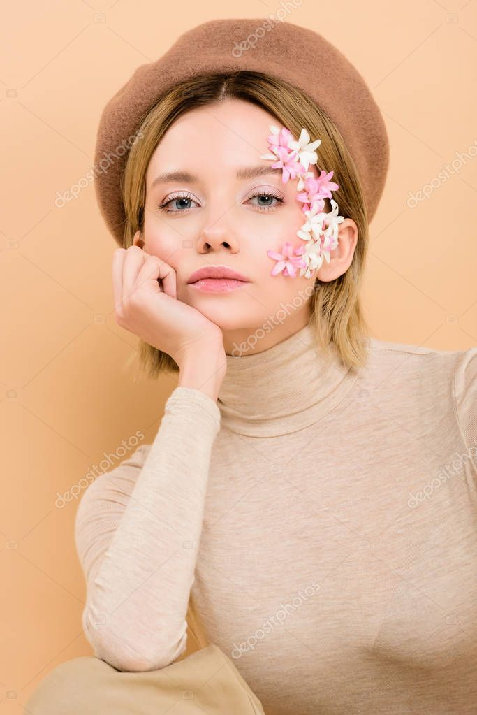 Serious woman with flowers on face looking at camera isolated on beige stock vector