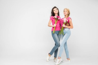 smiling women holding flowers and standing on grey background