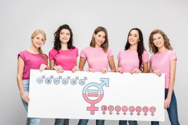 beautiful young women holding large sign with gender equality symbol isolated on grey