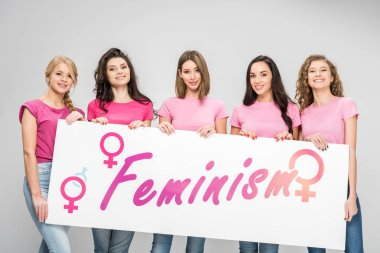 cheerful girls holding large sign with feminism lettering isolated on grey