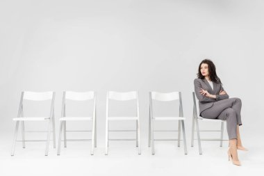 Confident woman sitting with crossed arms and crossed legs on chair isolated on grey stock vector