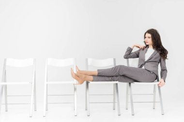 serious woman putting legs on chair while sitting isolated on grey