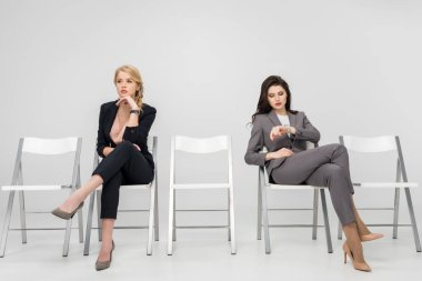 Businesswoman sitting with crossed legs and looking at watch near pensive female coworker isolated on grey stock vector