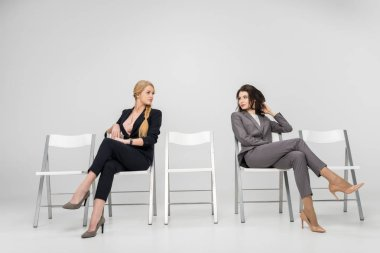 Businesswomen sitting with crossed legs and looking at each other isolated on grey stock vector