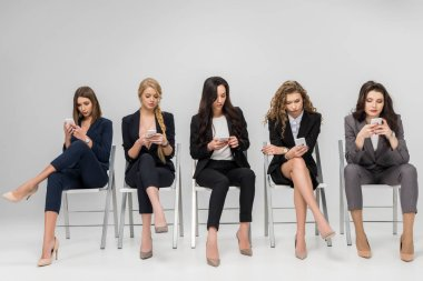 Attractive businesswomen using smartphones while sitting on chairs isolated on grey stock vector
