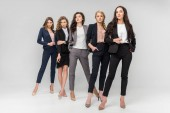 beautiful successful young women standing with hands in pockets on grey background