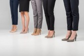 Photo cropped view of women standing in hight heel shoes on grey background