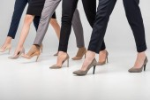 Photo cropped view of women walking in high heel shoes on grey background