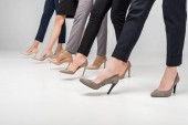 Photo cropped view of businesswomen walking in high heel shoes on grey background