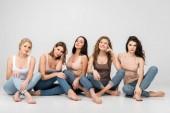 schöne Mädchen lächeln, während sie mit überkreuzten Beinen auf grauem Hintergrund sitzen
