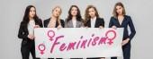 atraktivní podnikatelky drží velký znak s nápisem feminismus izolované Grey